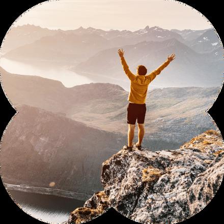 Homem no topo de uma montanha estendendo os braços